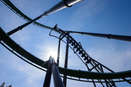 Silhouette of roller coaster track on blue sky backgrounds