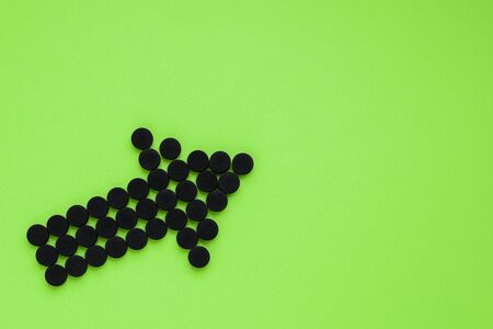 Medical activated carbon in the form of an arrow on a green background. Top view, copy space.
