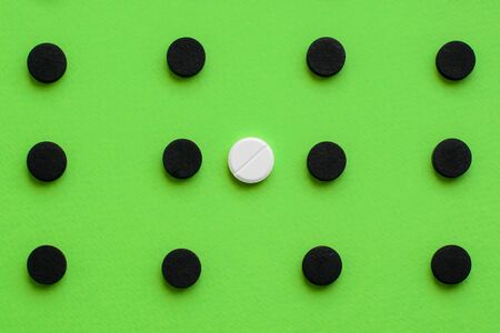 Conceptual medical background with black capsules of activated charcoal with a white pill on a green background. Top view, copy space.