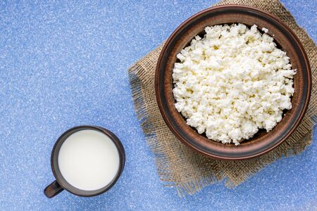 Homemade cottage cheese in a bowl on a sack and wooden mug with milk on a blue table. top view. copy space.