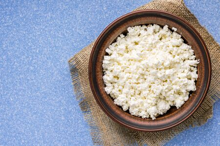 Homemade cottage cheese in a bowl on a sack and on a blue table. top view. Zdjęcie Seryjne