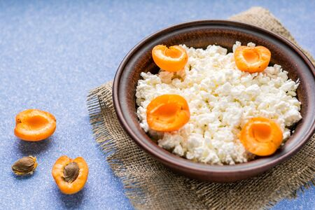 Homemade cottage cheese with fresh apricots in a bowl on a sack and on a blue table. side view.