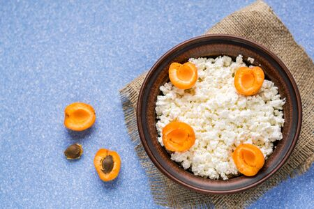 Homemade cottage cheese with fresh apricots in a bowl on a sack and on a blue table. top view. copy space.