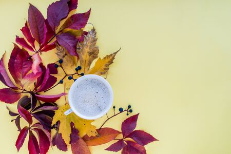 Autumn composition. mug of cappuccino and yellow and red leaves with berries on a yellow background. autumn background. flat lay, top view, copy space