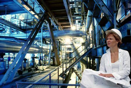 vrouw ingenieur, pijpen, buizen, machines en stoomturbine in een energiecentrale Stockfoto