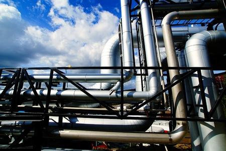 Zona industrial, tuberías de acero y válvulas contra el cielo azul Foto de archivo