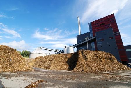 bio-energiecentrale met opslag van houten brandstof (biomassa) tegen de blauwe hemel