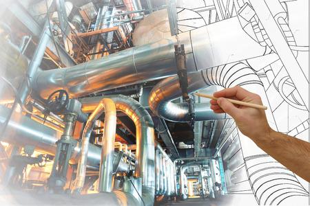 남자의 손은 현대 산업 발전소의 사진과 함께 공장의 설계를 그립니다