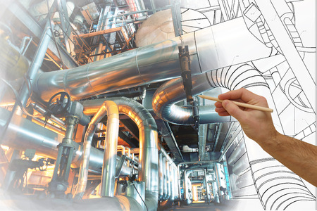man's hand draws a design of factory combined with photo of modern industrial power plant