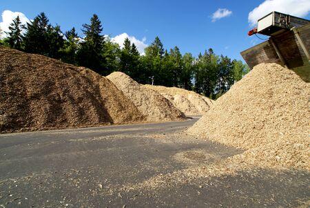 el almacenamiento del combustible de madera (biomasa) contra el cielo azul
