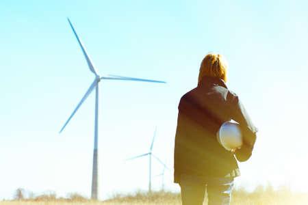 Vrouweningenieur of architect met witte veiligheidshoed en windturbines op achtergrond Stockfoto