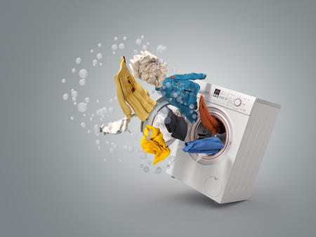 Washing machine and flying clothes on grey background Stock Photo