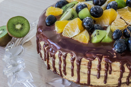 caked: honey sponge cake is decorated with fruits and chocolate stains