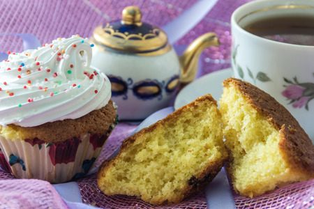 unwholesome: Split biscuit muffin and muffin, decorated with whipped protein cream, on the background cup of tea and teapot Stock Photo