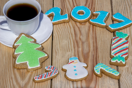 Gingerbreads are decorated for the new 2017 year and cup of coffee (can be used as card)