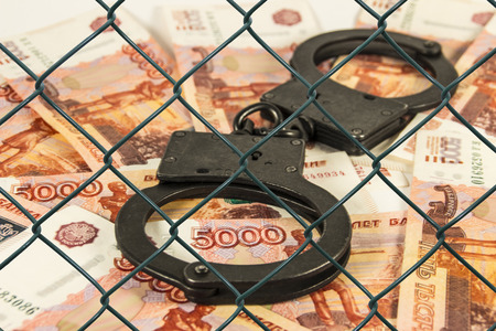 The cuffs on the background of Russian money under the net (in custody)