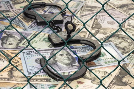 handcuffs with dollars behind bars
