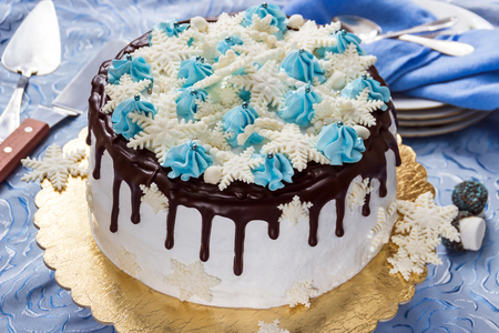 Beautiful cream cake decorated with chocolate leaks, cream and sugar snowflakes from mastic, on the background of plates, teaspoons and pallet knife Stock Photo