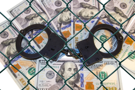 deeds: grid on the blurred background of money with handcuffs
