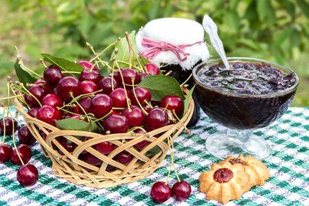 Basket of cherries, cherry jam with biscuit, cherry jam jar on background of cherry tree