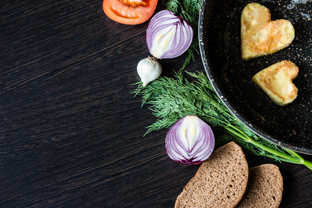 Fried eggs in the shape of a heart in a frying pan, near which lay bread slices, red onion, tomato, garlic and dill on dark wooden table