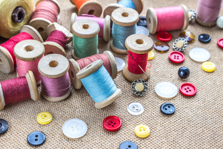 stitchwork: sewing tools (many different colorful thread, needle, many different buttons) on wooden background