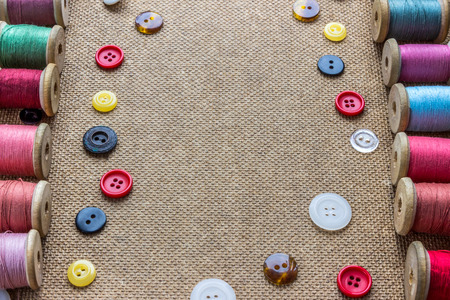 sewing tools (many different colorful thread, many different buttons) on wooden background