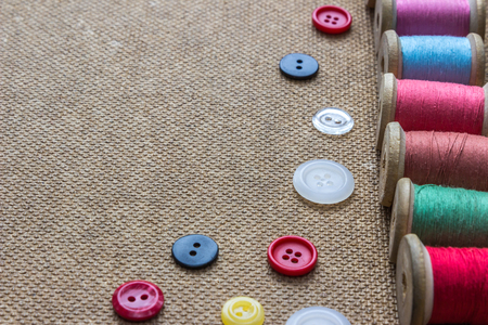 stitchcraft: sewing tools (many different colorful thread, many different buttons) on wooden background
