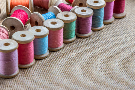 stitchwork: many different colorful thread on wooden background