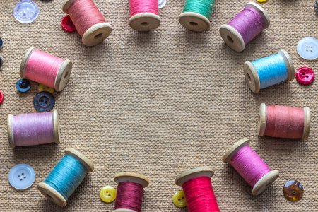 stitchwork: sewing tools (many different colorful thread, different buttons) on wooden background
