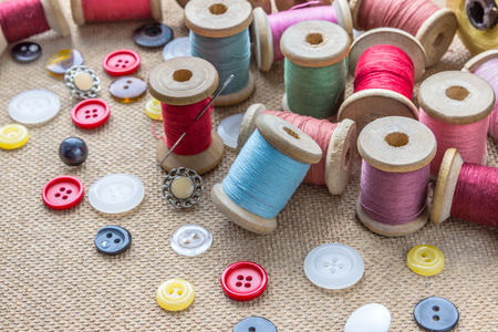stitchcraft: sewing tools (many different colorful thread, needle, many different buttons) on wooden background