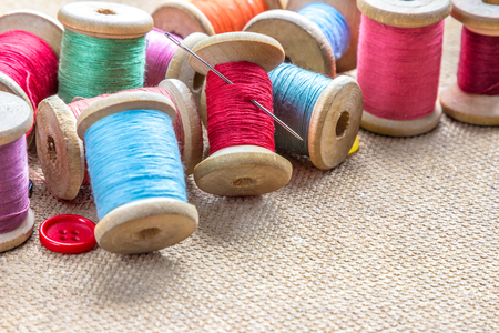 stitchcraft: sewing tools (many different colorful thread, needle, buttons) on wooden background Stock Photo