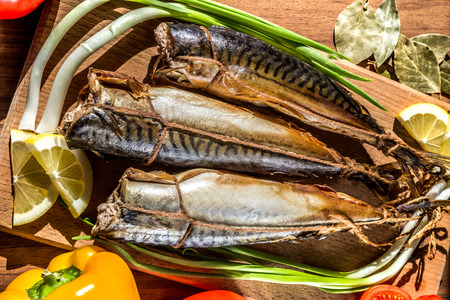 smoked fish mackerel on a cutting Board on a background of vegetables