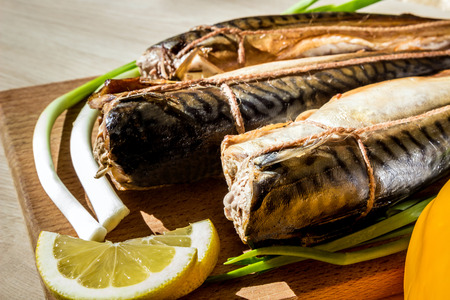 Smoked fish mackerel on wooden cutting board on wooden table