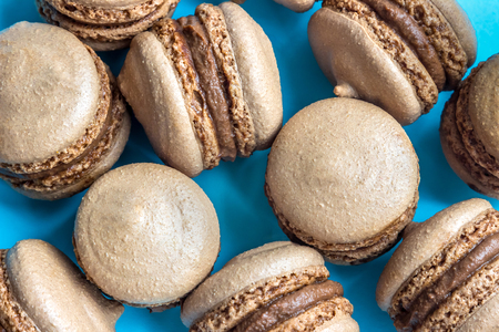 sunflower seeds: Chocolate macaron or macaroon cake on blue background, top view
