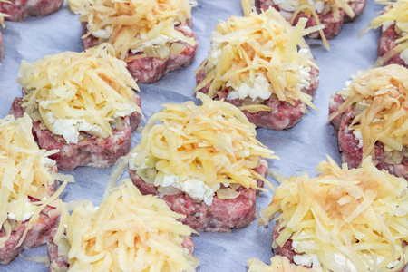Meat stacks (raw fresh pork cutlets with fried onions and boiled eggs and potatoes) in the shape of a flower on parchment paper