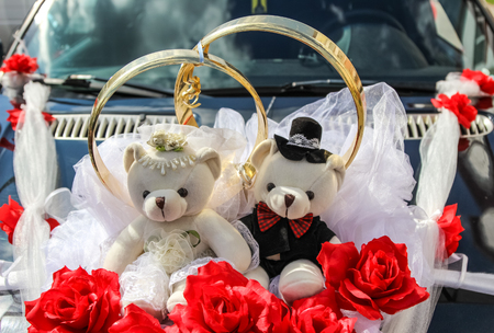Wedding rings and couple of teddy bears on car (decoration)