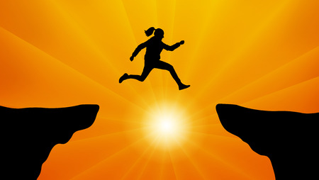 Silhouette of the girl jumping over the cliff.