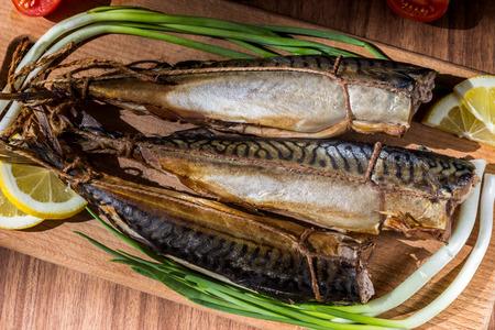 mackerel smoked fish on wooden hardboard on wooden table Stock Photo