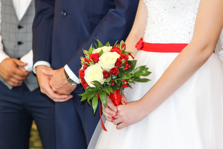 Wedding bouquet in hands of bride. The bride and groom in the registry office Stock Photo