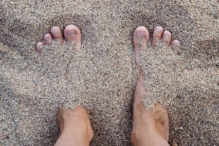 Women's feet without manicure in the pebbles on the beach. The concept of vacation.