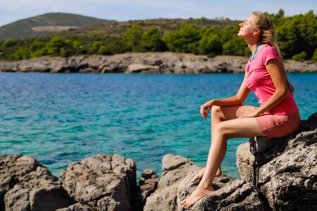 Beautiful woman sits on rock against the azure sea and breathes fresh air on vacation