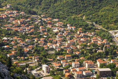 Red roofs of houses and buildings, village near Kotor in Montenegro, aerial view.