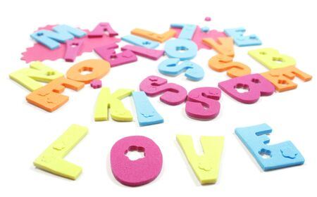 VIew of  letters forming the word love at the forefront, and love, kiss, be mine in the background. Isoalated over white