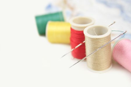 Versatile craft, sewing background: threads and needles on white  Stock Photo