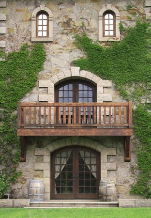 Architectural detail of a castle facade, entrance. Windows, balcony, front door, wall covered by ivy