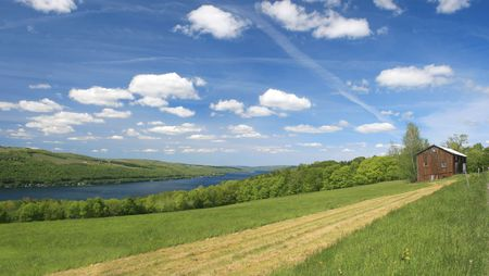VIew of a scenic, green pasture or agricultural field, with house and a view of Keuka Lake, one of eleven fingerlakes in upstate New York