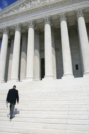 governmental: Professional, business man in black suit walking up the steps of the US Supreme Court