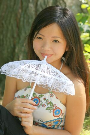 glance: Portrait of a young asian female with a white lacy umbrella Stock Photo