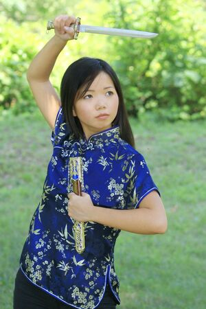 glance: Portrait of a young asian female in traditional Vietnamese dress with sword Stock Photo